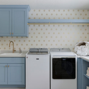 Dedicated laundry room - traditional l-shaped beige floor dedicated laundry room idea in Other with a drop-in sink, shaker cabinets, blue cabinets, laminate countertops, a side-by-side washer/dryer and multicolored walls