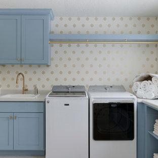 Klassisk inredning av en l-formad tvättstuga enbart för tvätt, med en nedsänkt diskho, skåp i shakerstil, blå skåp, laminatbänkskiva, en tvättmaskin och torktumlare bredvid varandra, flerfärgade väggar och beiget golv