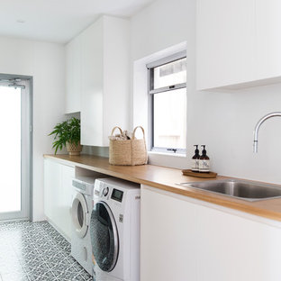 Photo of a mid-sized contemporary single-wall dedicated laundry room in Gold Coast - Tweed with a drop-in sink, flat-panel cabinets, white cabinets, wood benchtops, white walls, a side-by-side washer and dryer, multi-coloured floor and beige benchtop.