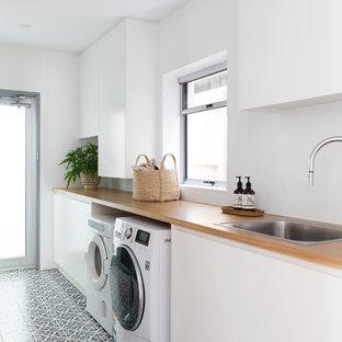 Inspiration för en mellanstor funkis beige linjär beige tvättstuga enbart för tvätt, med en nedsänkt diskho, släta luckor, vita skåp, träbänkskiva, vita väggar, en tvättmaskin och torktumlare bredvid varandra och flerfärgat golv
