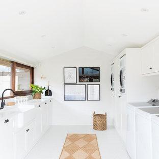 Inspiration för en mycket stor funkis parallell tvättstuga enbart för tvätt, med en rustik diskho, skåp i shakerstil, vita skåp, bänkskiva i kvarts, vita väggar, klinkergolv i porslin, vitt golv och en tvättmaskin och torktumlare bredvid varandra