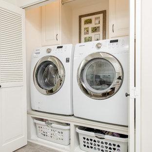 Klassisk inredning av en liten linjär liten tvättstuga, med luckor med upphöjd panel, vita skåp, bänkskiva i kvarts, vita väggar, klinkergolv i porslin och en tvättmaskin och torktumlare bredvid varandra