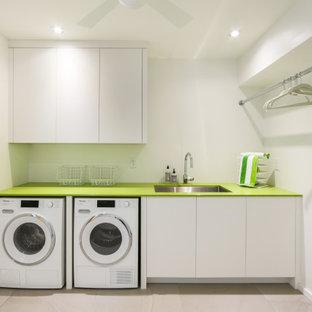 Inredning av en modern liten gröna linjär grönt tvättstuga enbart för tvätt, med en undermonterad diskho, släta luckor, vita skåp, bänkskiva i koppar, vita väggar, en tvättmaskin och torktumlare bredvid varandra, beiget golv och klinkergolv i porslin