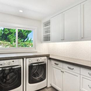 Exempel på en mellanstor klassisk grå u-formad grått tvättstuga enbart för tvätt, med vita skåp, en tvättmaskin och torktumlare bredvid varandra, vita väggar, skåp i shakerstil, bänkskiva i kalksten, kalkstensgolv och grått golv