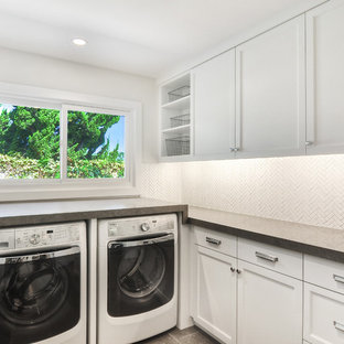 Inspiration for a mid-sized transitional u-shaped limestone floor and gray floor dedicated laundry room remodel in Orange County with white cabinets, a side-by-side washer/dryer, white walls, gray countertops, shaker cabinets and limestone countertops