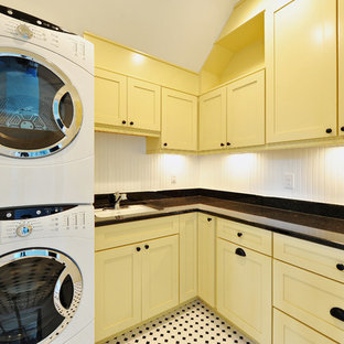This is an example of a traditional laundry room in Philadelphia with a stacked washer and dryer and multi-coloured floor.