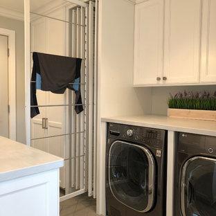 Immagine di una lavanderia multiuso chic di medie dimensioni con lavello stile country, ante con riquadro incassato, ante bianche, pareti grigie, pavimento con piastrelle in ceramica, lavatrice e asciugatrice nascoste, pavimento marrone e top grigio