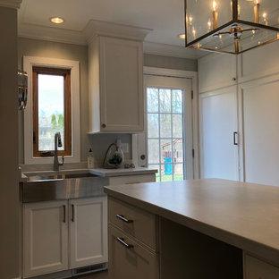 Exempel på ett mellanstort klassiskt grå parallellt grått grovkök, med luckor med infälld panel, vita skåp, en rustik diskho, grå väggar, klinkergolv i keramik, tvättmaskin och torktumlare byggt in i ett skåp och brunt golv