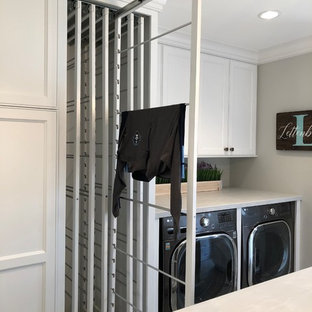 This is an example of a medium sized traditional galley utility room in Milwaukee with a belfast sink, recessed-panel cabinets, white cabinets, grey walls, ceramic flooring, a concealed washer and dryer, brown floors and grey worktops.