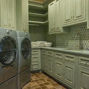 Esempio di una grande lavanderia multiuso rustica con lavello a vasca singola, ante con bugna sagomata, ante con finitura invecchiata, lavatrice e asciugatrice affiancate e pareti verdi