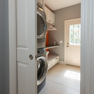 This is an example of a small traditional single-wall utility room in Indianapolis with recessed-panel cabinets, grey cabinets, granite worktops, grey walls, ceramic flooring, a stacked washer and dryer, white floors and black worktops.