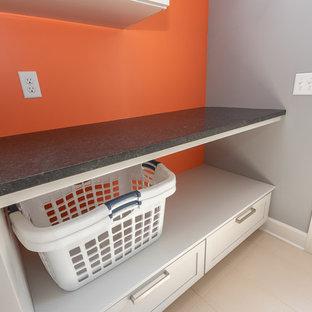 Foto di una piccola lavanderia multiuso classica con ante con riquadro incassato, ante grigie, top in granito, pareti grigie, pavimento con piastrelle in ceramica, lavatrice e asciugatrice a colonna, pavimento bianco e top nero