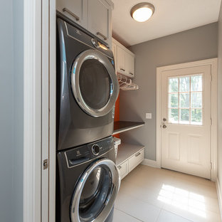 Inspiration for a small traditional single-wall utility room in Indianapolis with recessed-panel cabinets, grey cabinets, granite worktops, grey walls, ceramic flooring, a stacked washer and dryer, white floors and black worktops.