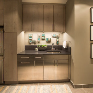 Large modern utility room in Chicago with stainless steel cabinets, beige walls, porcelain floors and a stacked washer and dryer.