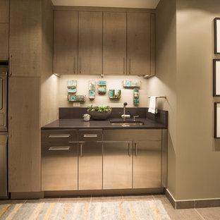 Ispirazione per una grande lavanderia multiuso minimalista con ante in acciaio inossidabile, pareti beige, pavimento in gres porcellanato e lavatrice e asciugatrice a colonna
