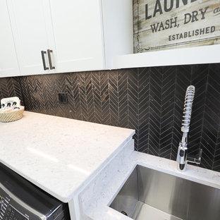 Esempio di una piccola sala lavanderia con lavello sottopiano, ante in stile shaker, ante bianche, top in quarzo composito, pareti bianche, pavimento con piastrelle in ceramica, lavatrice e asciugatrice affiancate, pavimento nero e top multicolore