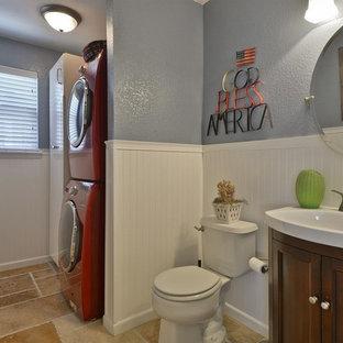 Идея дизайна: маленькая параллельная универсальная комната в стиле модернизм с одинарной раковиной, белыми фасадами, синими стенами, полом из травертина, с сушильной машиной на стиральной машине и коричневым полом