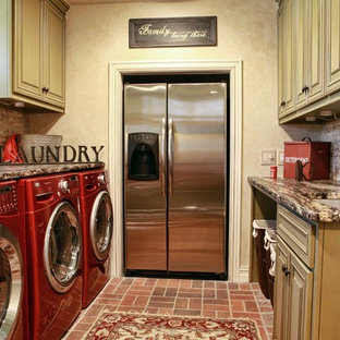 Elegant brick floor and red floor laundry room photo in Other