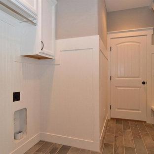 Réalisation d'une buanderie parallèle style shabby chic multi-usage et de taille moyenne avec un placard avec porte à panneau encastré, des portes de placard blanches, un mur gris, un sol en ardoise et des machines côte à côte.