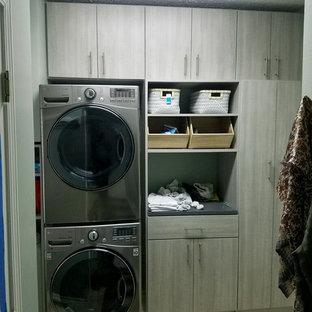 Ispirazione per una sala lavanderia contemporanea di medie dimensioni con ante lisce, ante grigie, top in laminato, pavimento in terracotta, lavatrice e asciugatrice a colonna, top grigio e pavimento beige