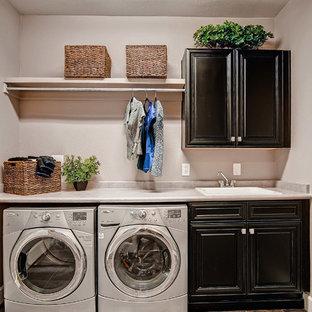 Foto på en vintage tvättstuga, med svarta skåp och en tvättmaskin och torktumlare bredvid varandra