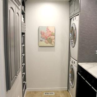 Aménagement d'une petit buanderie parallèle classique dédiée avec un placard avec porte à panneau surélevé, des portes de placard grises, un plan de travail en stratifié, un mur blanc, un sol en linoléum et des machines superposées.