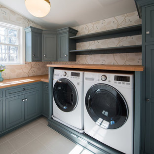 Example of a transitional l-shaped porcelain tile dedicated laundry room design in Philadelphia with a drop-in sink, blue cabinets, wood countertops, multicolored walls, a side-by-side washer/dryer and recessed-panel cabinets