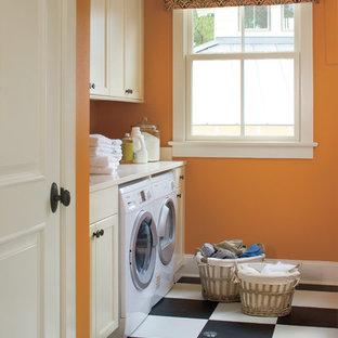 Exempel på en klassisk vita vitt tvättstuga, med orange väggar och flerfärgat golv
