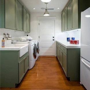 Foto på en stor vintage vita parallell tvättstuga enbart för tvätt, med en rustik diskho, skåp i shakerstil, vita väggar, mellanmörkt trägolv, en tvättmaskin och torktumlare bredvid varandra, gröna skåp och marmorbänkskiva