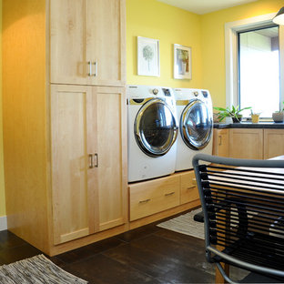 This is an example of a large industrial separated utility room in Other with a belfast sink, light wood cabinets, yellow walls, porcelain flooring, a side by side washer and dryer, recessed-panel cabinets and concrete worktops.