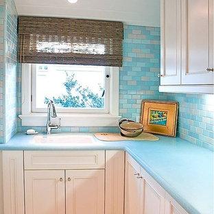 Inspiration för stora klassiska l-formade tvättstugor enbart för tvätt, med en undermonterad diskho, skåp i shakerstil, vita skåp, bänkskiva i glas, vita väggar, klinkergolv i porslin och en tvättmaskin och torktumlare bredvid varandra