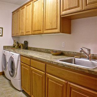 Inspiration för stora amerikanska tvättstugor enbart för tvätt, med en enkel diskho, luckor med upphöjd panel, granitbänkskiva, vita väggar, klinkergolv i keramik, en tvättmaskin och torktumlare bredvid varandra och skåp i mellenmörkt trä