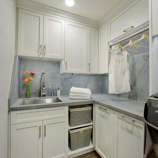 Foto di una lavanderia multiuso tradizionale di medie dimensioni con lavello sottopiano, ante in stile shaker, ante bianche, top in cemento, pareti marroni, parquet scuro, lavatrice e asciugatrice affiancate, pavimento marrone e top grigio