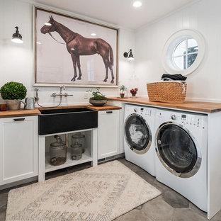 Cette image montre une buanderie rustique en L avec un évier de ferme, un placard avec porte à panneau encastré, des portes de placard blanches, un plan de travail en bois, un sol gris et un plan de travail marron.