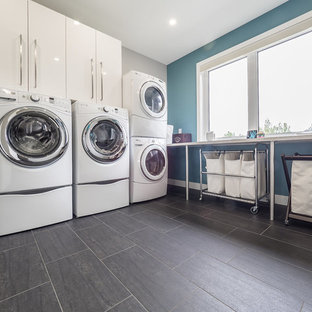 Photo of a large modern l-shaped separated utility room in Edmonton with a double-bowl sink, flat-panel cabinets, white cabinets, composite countertops, blue walls, porcelain flooring, a side by side washer and dryer and grey floors.
