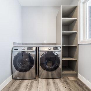Foto di una grande sala lavanderia con top in quarzo composito, pareti grigie, pavimento in vinile, lavatrice e asciugatrice affiancate e pavimento multicolore
