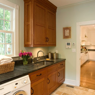 Example of a large classic beige floor and limestone floor utility room design in Other with green walls, an undermount sink, recessed-panel cabinets, medium tone wood cabinets, soapstone countertops, a side-by-side washer/dryer and black countertops