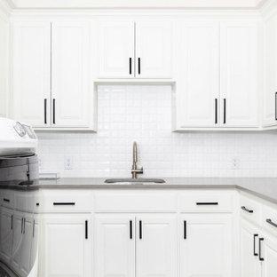 Bild på en mellanstor vintage grå u-formad grått tvättstuga enbart för tvätt, med en allbänk, skåp i shakerstil, vita skåp, bänkskiva i kvarts, vitt stänkskydd, stänkskydd i porslinskakel, vita väggar, betonggolv, en tvättmaskin och torktumlare bredvid varandra och grått golv