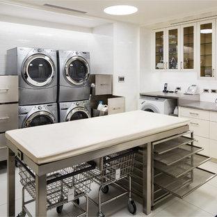 Idéer för att renovera en mycket stor vintage u-formad tvättstuga enbart för tvätt, med en undermonterad diskho, luckor med glaspanel, vita skåp, bänkskiva i rostfritt stål, vita väggar och en tvättpelare