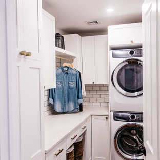 This is an example of a small midcentury l-shaped dedicated laundry room in Philadelphia with shaker cabinets, white cabinets, quartz benchtops, white splashback, subway tile splashback, white walls, porcelain floors, a stacked washer and dryer, black floor and white benchtop.