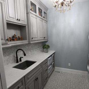 Immagine di una sala lavanderia vittoriana di medie dimensioni con lavello da incasso, ante con bugna sagomata, ante grigie, top in quarzite, paraspruzzi in marmo, pavimento con piastrelle in ceramica, lavatrice e asciugatrice a colonna, pavimento multicolore e top bianco