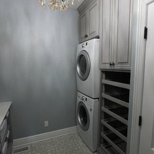 Inredning av en mellanstor flerfärgade parallell flerfärgat tvättstuga enbart för tvätt, med en undermonterad diskho, luckor med upphöjd panel, grå skåp, bänkskiva i kvartsit, flerfärgad stänkskydd, stänkskydd i marmor, grå väggar, betonggolv, en tvättpelare och grått golv