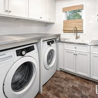 Foto di una piccola sala lavanderia classica con ante bianche, top in acciaio inossidabile, pareti bianche, pavimento con piastrelle in ceramica, lavatrice e asciugatrice affiancate, ante con riquadro incassato e lavello da incasso
