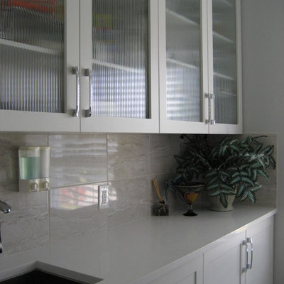 Laundry room - mid-sized contemporary laundry room idea in Other with an undermount sink, shaker cabinets, white cabinets, solid surface countertops, gray walls and a side-by-side washer/dryer