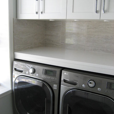 Laundry room - mid-sized contemporary laundry room idea in Other with an undermount sink, shaker cabinets, white cabinets, solid surface countertops, a side-by-side washer/dryer and gray walls
