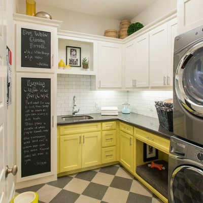Elegant l-shaped laundry room photo in Dallas with an undermount sink, shaker cabinets, yellow cabinets, white walls, a stacked washer/dryer and gray countertops