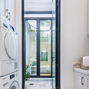 Small modern galley dedicated laundry room in San Francisco with a drop-in sink, shaker cabinets, white cabinets, marble benchtops, white walls, marble floors, a stacked washer and dryer, yellow floor and white benchtop.