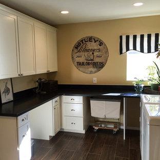 Foto di una lavanderia industriale con lavello sottopiano, ante in stile shaker, ante bianche, top in granito, pareti gialle, pavimento in gres porcellanato e lavatrice e asciugatrice affiancate