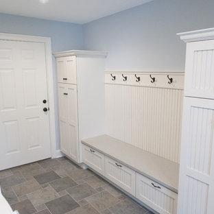 Пример оригинального дизайна: прачечная в классическом стиле с белыми фасадами, синими стенами, полом из керамической плитки, со стиральной и сушильной машиной рядом, разноцветным полом и фасадами с утопленной филенкой