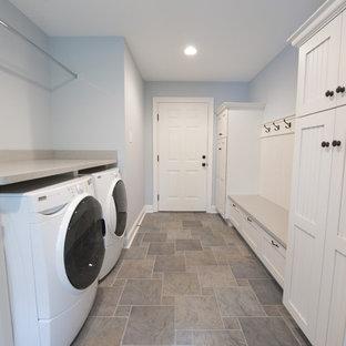 На фото: прачечные в классическом стиле с белыми фасадами, синими стенами, полом из керамической плитки, со стиральной и сушильной машиной рядом и разноцветным полом